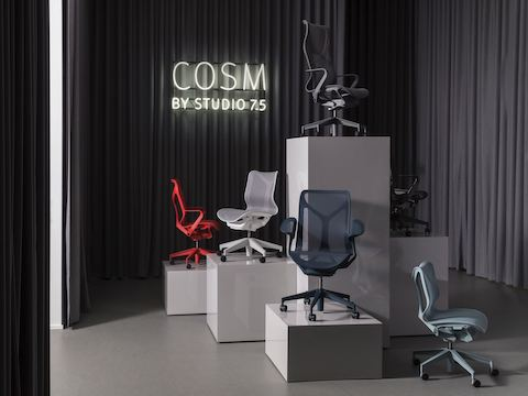 A variety of colors of low-, mid-, and high-back Cosm desk chairs on plinths of differing heights in a room surrounded by full-length dark gray curtains.