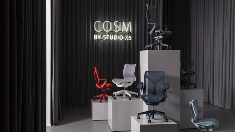 A variety of colours of low-, mid-, and high-back Cosm desk chairs on plinths of differing heights in a room surrounded by full-length dark grey curtains. Select to go to the Milan event page.
