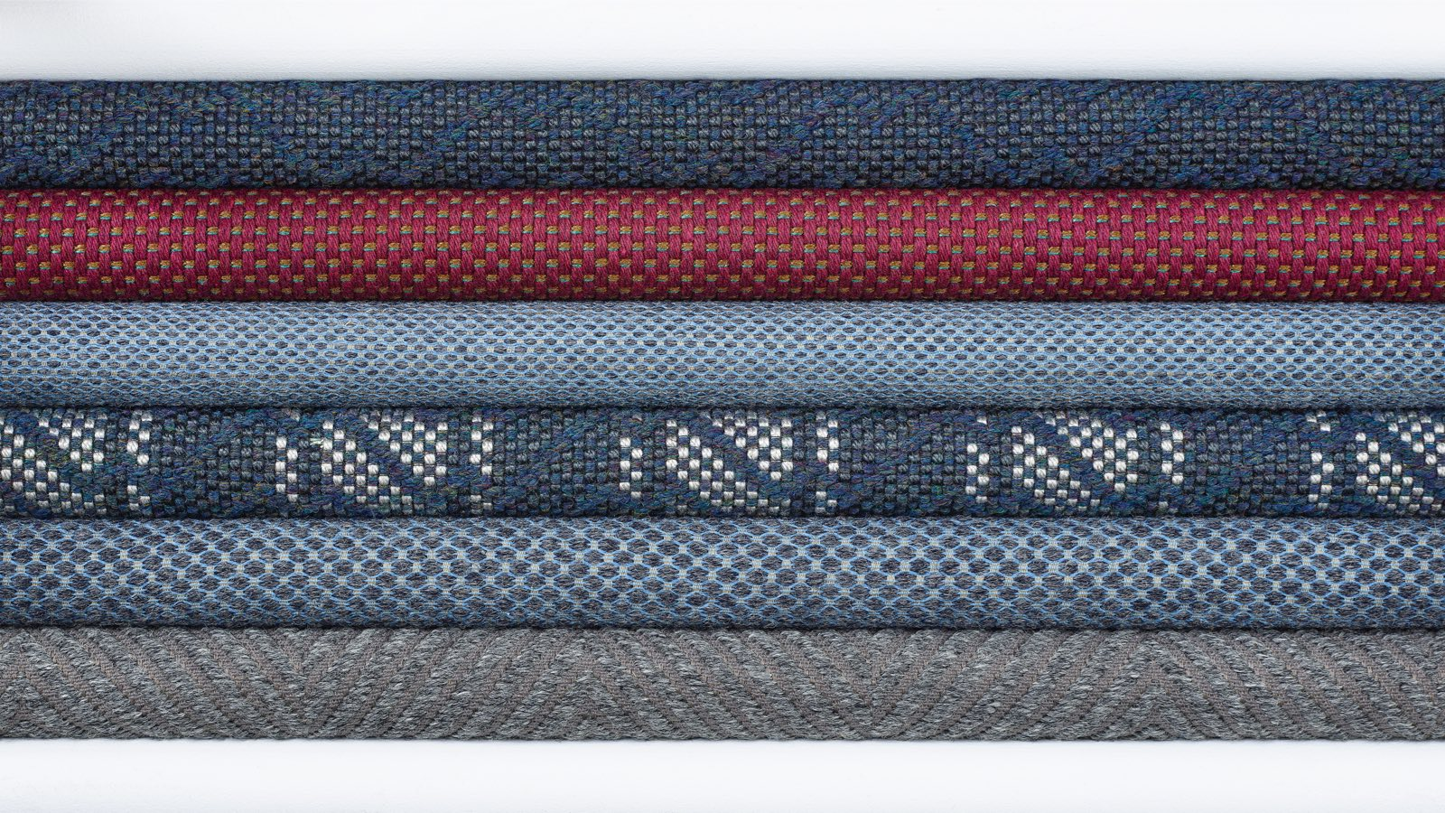 A stack of six blue, maroon, and gray textiles from the Taconic Collection.