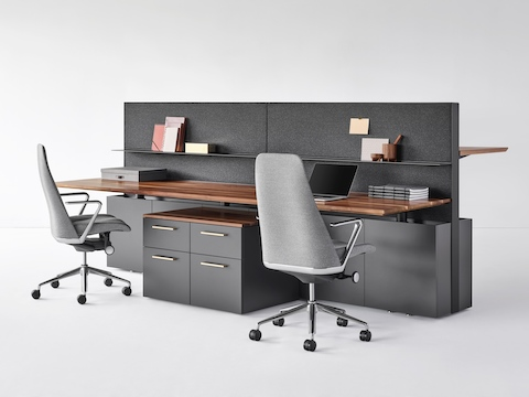 A bench system featuring Geiger One Casegoods. The two solid wood workstations in the forefront have mobile peds, shelves, and Taper Chairs. The workstation in the background is at standing height.