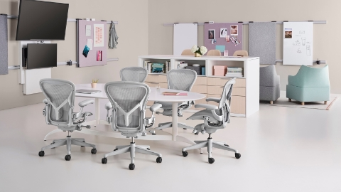 Light grey Aeron office chairs surround a table in a collaboration space.