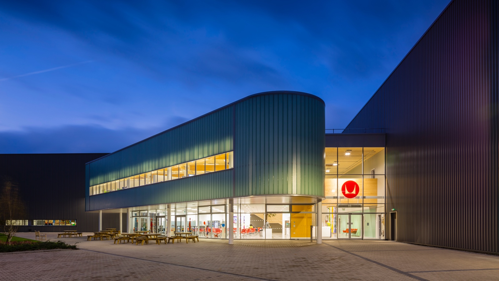 A night photo of the exterior of a Herman Miller manufacturing facility in the UK.