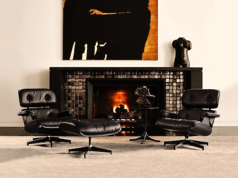 Two black leather Eames Lounge Chairs positioned in front of a fireplace.
