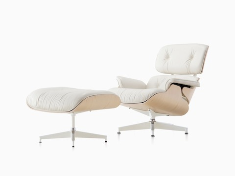 Angled view of an Eames Lounge Chair and Ottoman with white leather upholstery and a white ash veneer shell.