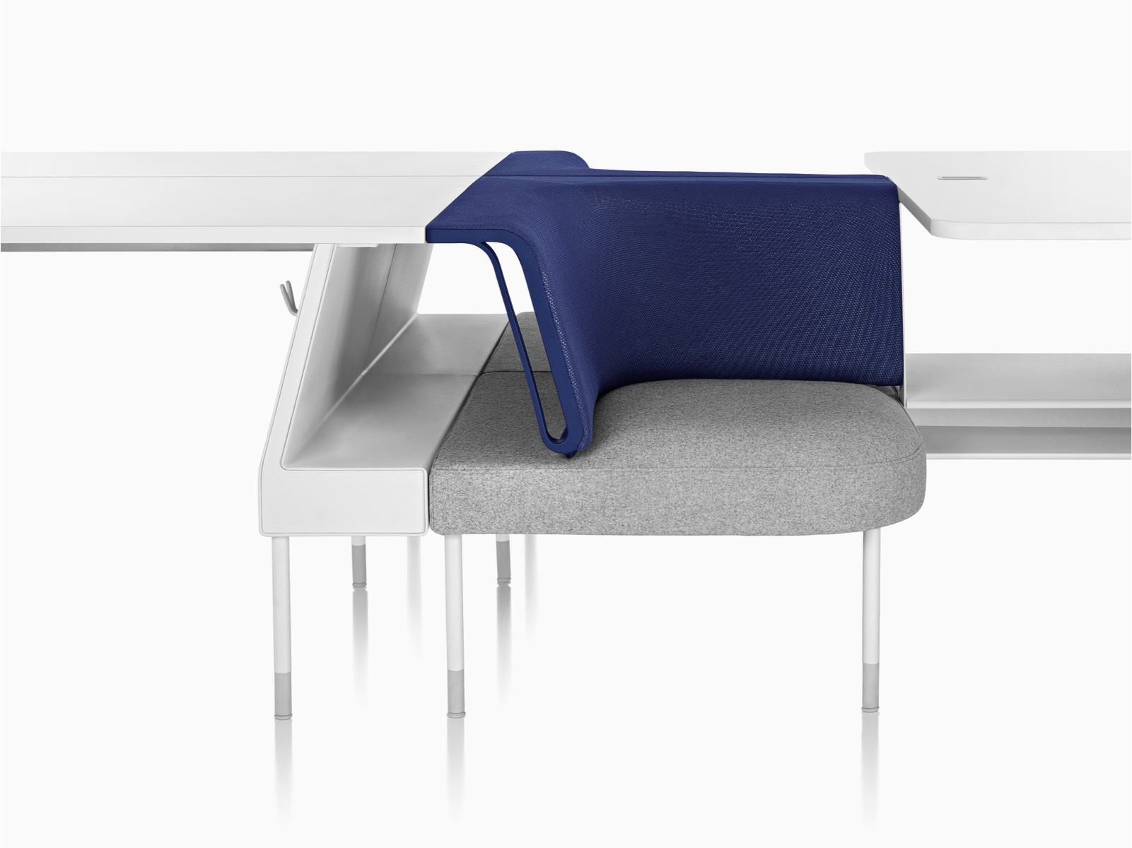 A Public Office Landscape social chair in grey and blue positioned between a desk and collaboration surface.