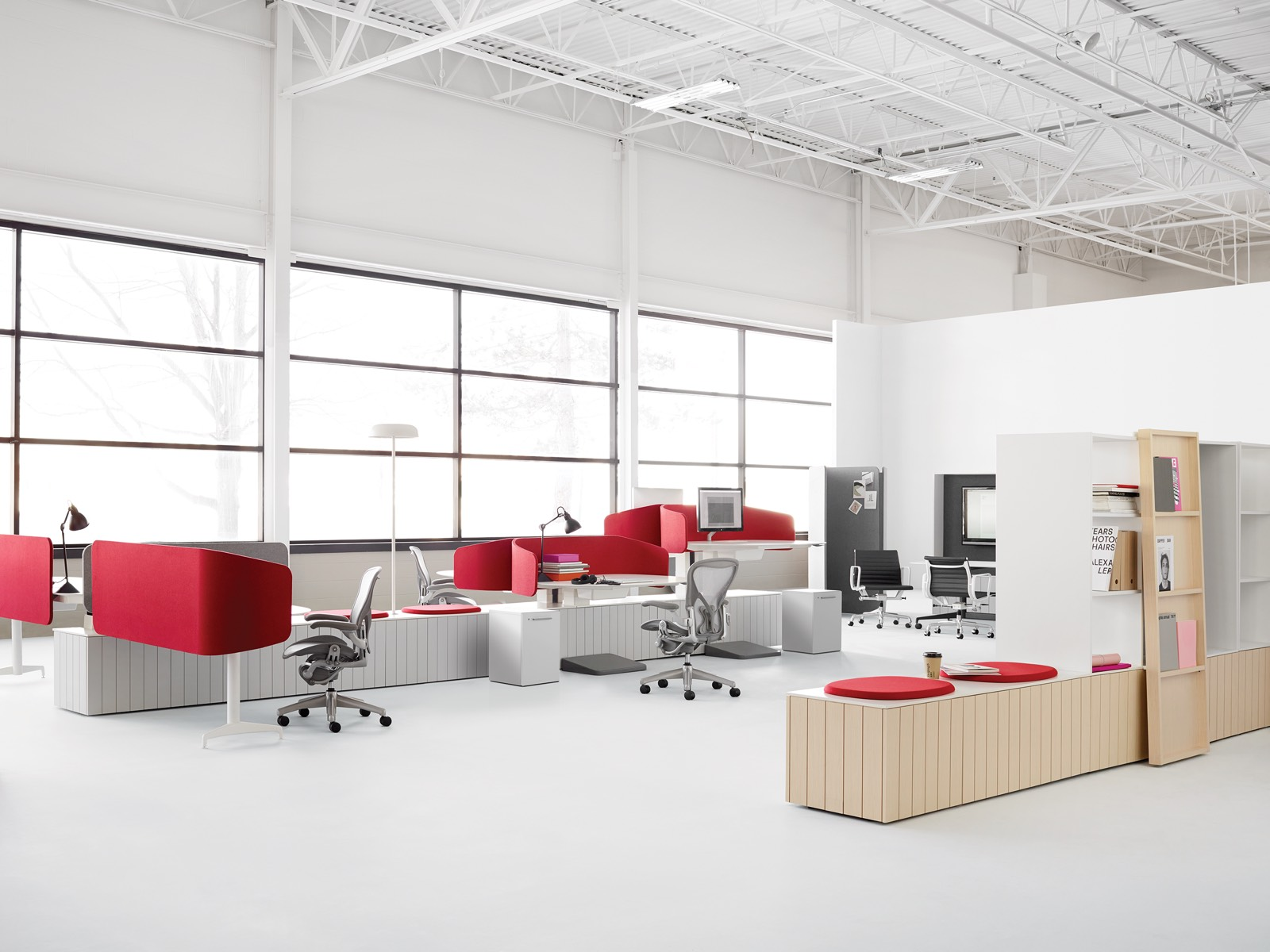 An open office in an industrial building featuring grey Aeron chairs at height-adjustable workstations with red privacy screens.