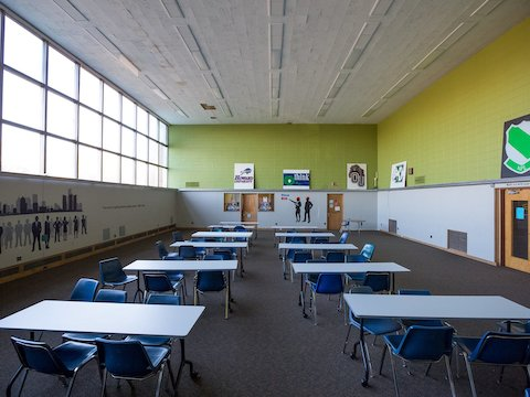 A classroom at Detroit's Cody High School outfitted with blue chairs, white tables, and new carpeting.