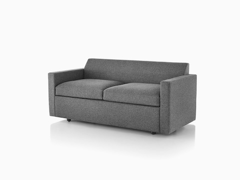Angled view of a Bevel Sofa with arms and grey upholstery.