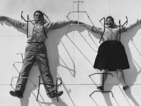 Charles and Ray Eames hold hands while lying on their backs with their arms outstretched.