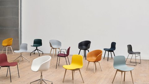 A collection of HAY lounge chairs in burgundy, oranges, yellow, white, light grays, blue, and blacks sit in a cluster in a blank office space.