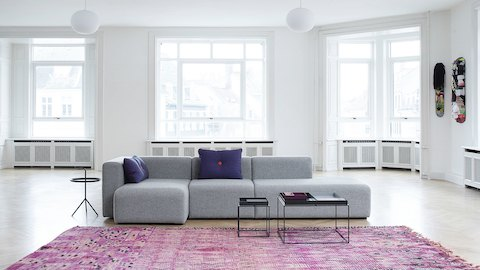 A modern light gray sofa and small metal side and coffee tables sit in the middle of a stark white room, with big windows and a pink Persian rug.