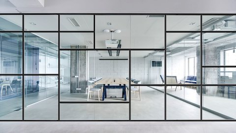 A Large Glass And Black Metal Wall With A Modern Geometric Pattern  Separates Two Open White
