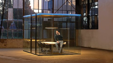 A freestanding cube room with glass and black metal walls and lit blue ceilings sits inside of a larger industrial space with paneled windows and cement walls. Inside the cube is a man talking on the phone, perched on a wood table and chairs.