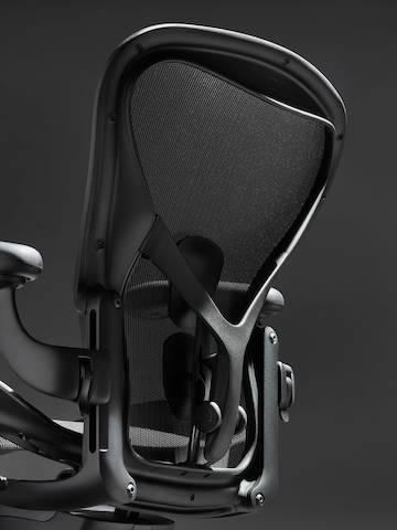Rückenlehne des Aeron Stuhls in Onyx Ultra Matte vor einem schwarzen Hintergrund mit ergonomischer Rückenstütze, schräg von hinten betrachtet.
