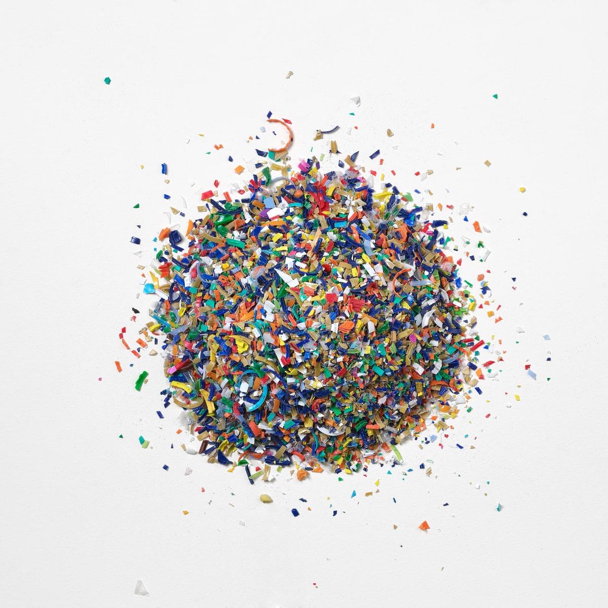 Ein runder Haufen und verstreute Teile von mehrfarbigem, recyceltem, gemahlenem Ocean Bound Plastic auf einem weißen Hintergrund.