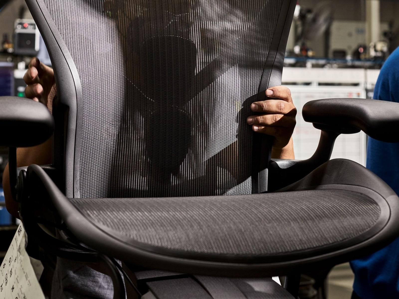 Ein Mann verstellt Sitz und Rückenlehne eines schwarzen Aeron Stuhls im Prüflabor von Herman Miller.