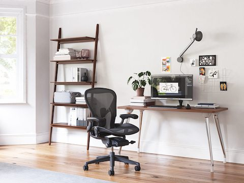 An AbakEnvironments Desk with a walnut top and polished pegs, with a graphite Aeron Chair in a light home office setting and Folk Ladder shelving.