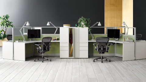 Black Aeron ergonomic desk chairs at Action Office 120 degree workstations with task lighting.