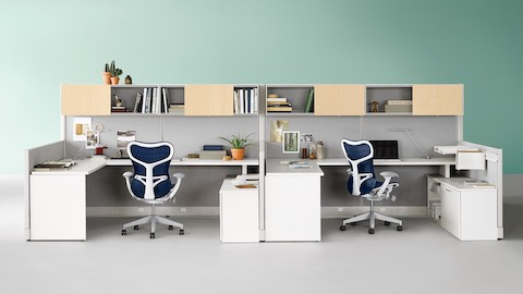 Blue Mirra 2 ergonomic desk chairs with white frames at Action Office workstations with overhead lateral storage.