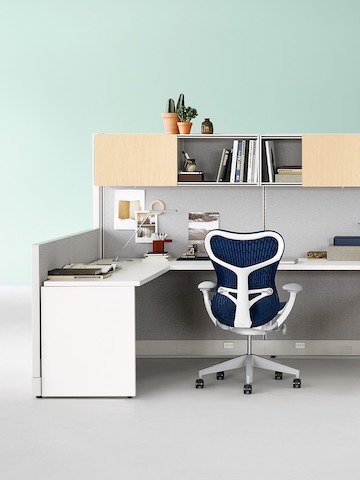 Navy blue Mirra 2 chair with white frame at an Action Office workstation with overhead storage.