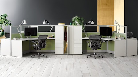 Action Office 120 degree workstations with monitors, task lighting, locker storage, and black Aeron ergonomic desk chairs.