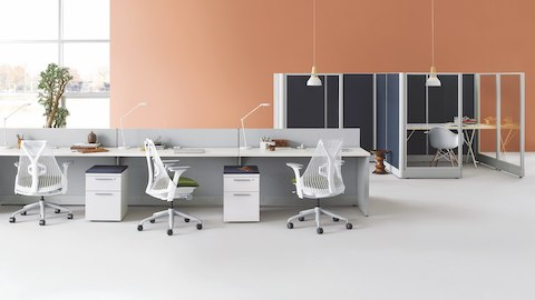 White Sayl ergonomic office chairs at Action Office workstations with storage pedestals near a pair of Action Office private offices.
