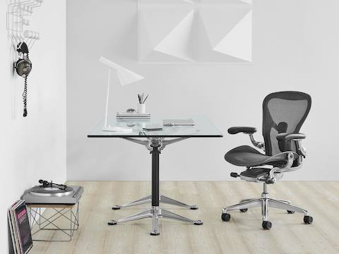 Black Aeron ergonomic desk chair with polished aluminum base at a Burdick Group glass-top table.