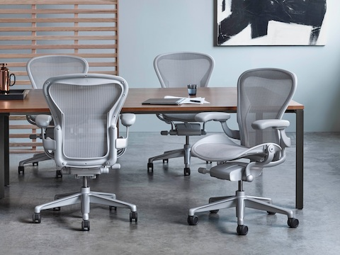 Conference room with four light gray Aeron office chairs around a Layout Studio table with a veneer top.