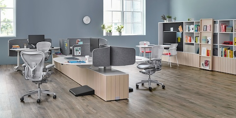 Light grey Aeron office chairs complement a collaboration space featuring Locale workstations with a low workbase, privacy screens, and wall storage.