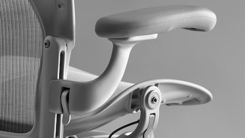 Close-up of the Pellicle mesh back and the arm adjustment thumb latch on a light gray Aeron office chair.