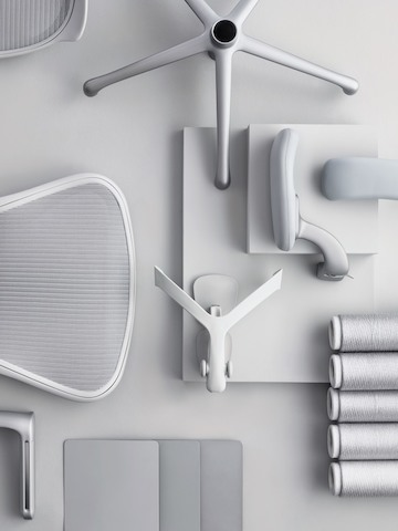 Overhead view of a disassembled light gray Aeron office chair, including five-star base, arms, and back support.