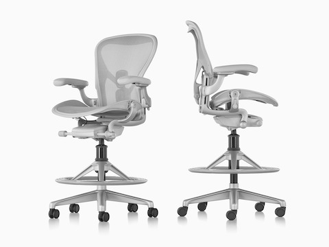 Views from an angle and profile of two light gray Aeron Stools.