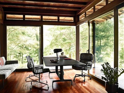 A black AGL table used as a desk in a glass-walled home office with a view of trees outside.