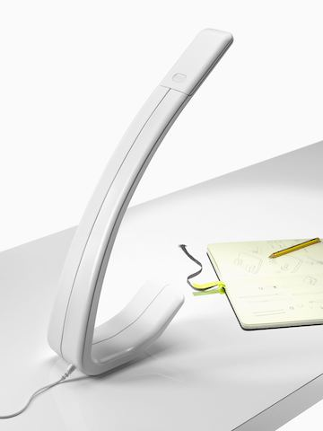 A single-piece Amble Task Light illuminates a notepad on a work surface.