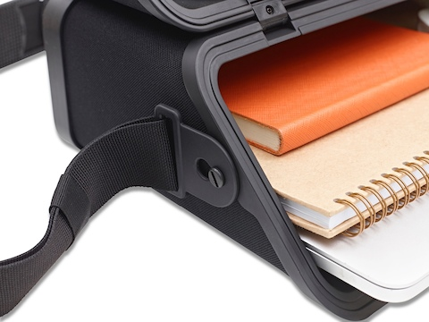 An Anywhere Case with a strap, positioned horizontally and containing a book, journal and laptop.