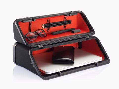 An Anywhere Case with a red lining, positioned horizontally and containing eyeglasses, writing utensils, and a laptop.