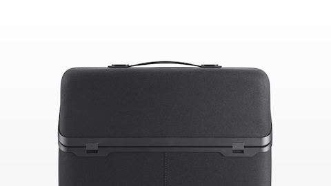 A closed, upright black Anywhere Case with a handle on top for carrying.
