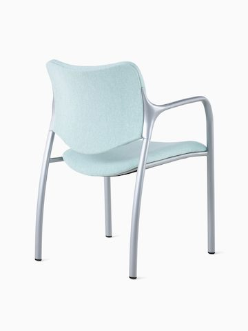 An Aside Chair with light green upholstered seat and back, viewed from the back at an angle.