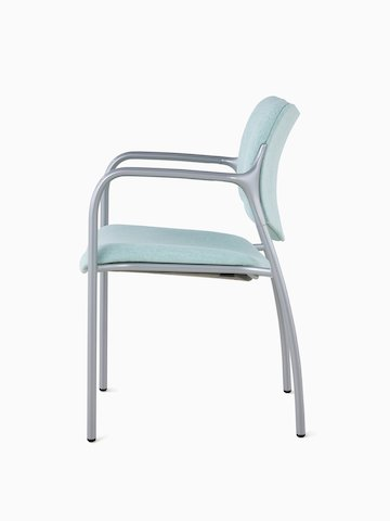 An Aside Chair with light green upholstered seat and back, viewed from the side.