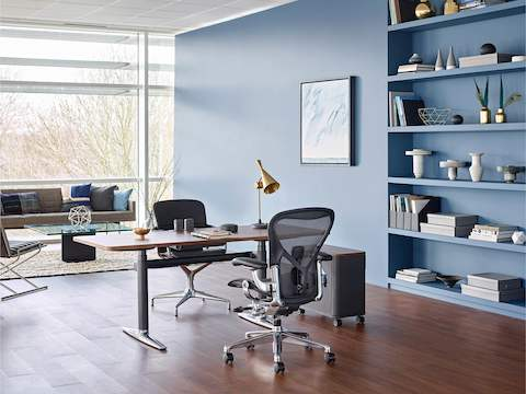 A black Aeron office chair paired with an Atlas Office Landscape desk in a private office with lounge seating and a window wall.