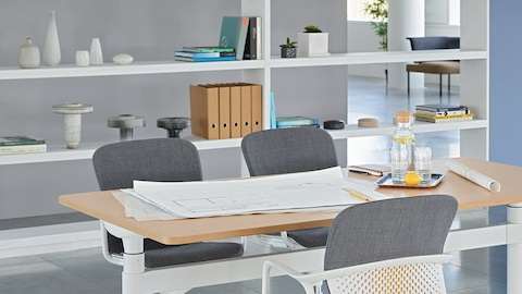An open meeting space featuring a height-adjustable Atlas Office Landscape table and three grey Keyn chairs.