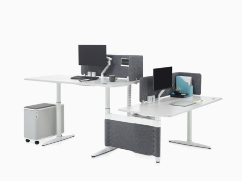 Height-adjustable Atlas Office Landscape desks in a 90-degree configuration, one at standing height and one at seated height.