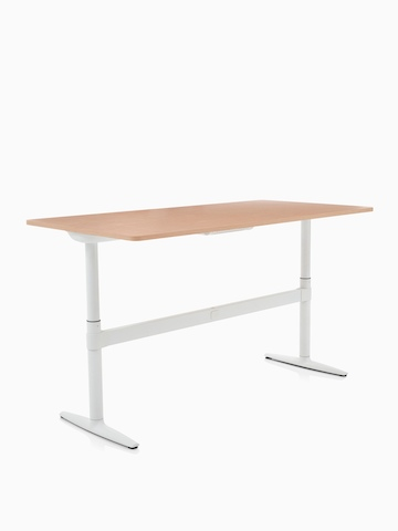 An adjustable Atlas Office Landscape desk with a woodgrain top, positioned at standing height and viewed at an angle.
