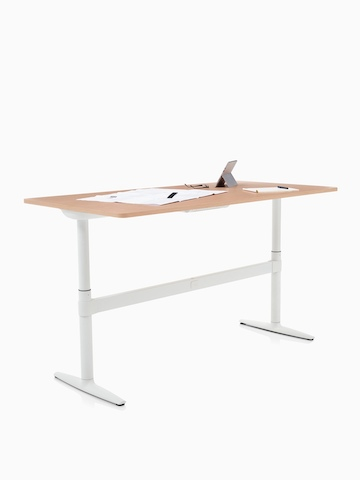 An Atlas Office Landscape desk positioned at standing height, with papers and a tablet on top. Select to go to the Atlas Office Landscape product page.