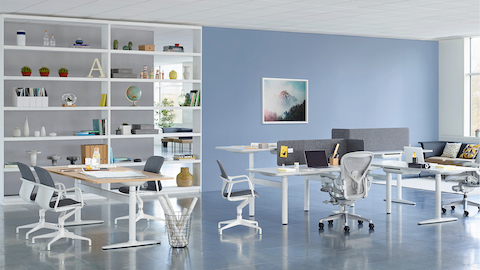 A collaboration setting featuring a cluster of sit-to-stand desks and a rectangular table from Atlas Office Landscape.
