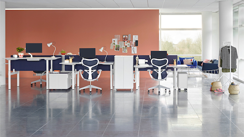 An open benching setup with height-adjustable Atlas Office Landscape desks at different heights and blue Mirra 2 office chairs.