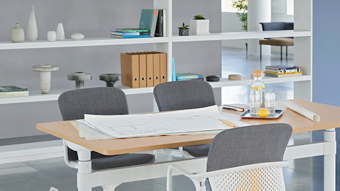 An open meeting space featuring a height-adjustable Atlas Office Landscape table and three gray Keyn chairs.