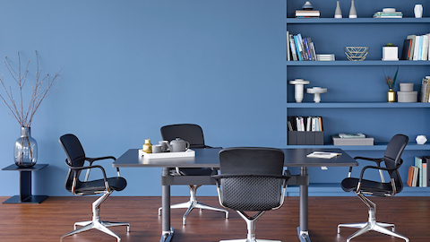 Four Keyn side chairs surround a rectangular Atlas Office Landscape table with a black top.