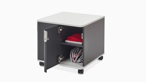 A bicycle helmet and red fabric fill an open Atlas Storage unit, viewed at an angle.