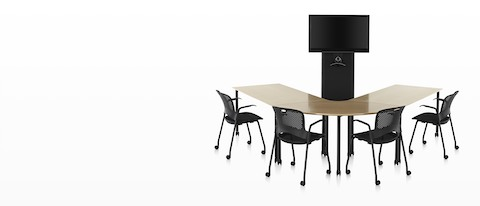 Black Caper office chairs around a u-shaped wood top table facing a black AV/VC One cart with large digital display and webcam.